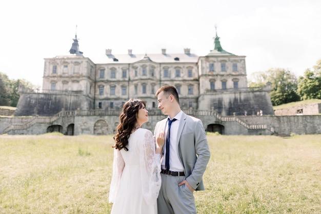 Couple de mariage asiatique fabuleux posant devant un vieux château médiéval, étreignant et embrassant par une journée ensoleillée.