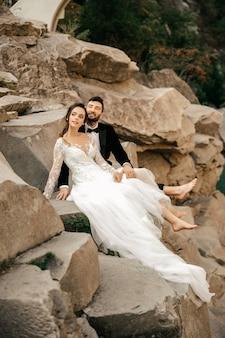 Couple de mariage assis et étreignant sur le fond d'une rivière de pierre.
