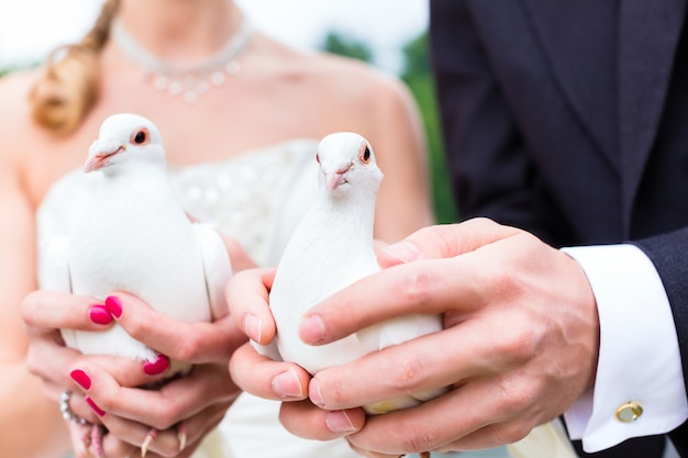 Couple de mariage au mariage avec des colombes blanches