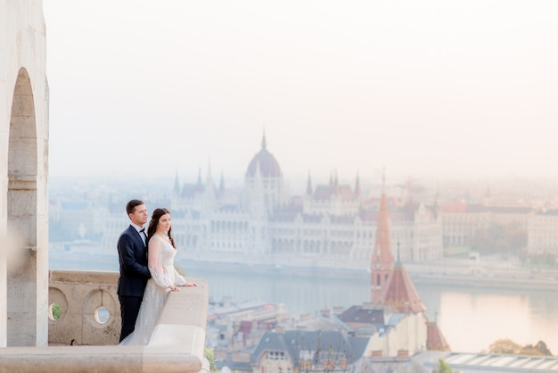 Couple de mariage sur le balcon en pierre d'un ancien bâtiment historique avec une vue imprenable sur budapest