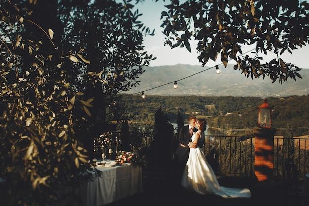 Couple de mariage bisous debout sur le porche avec table de dîner et lumières du soir