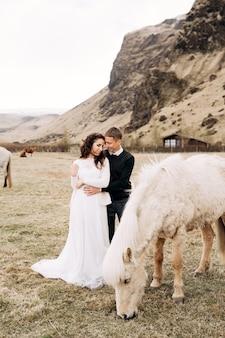 Un Couple De Mariage Et Un Cheval De Couleur Crème Photo Premium