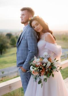 Couple de mariage dans la chaude soirée d'été près de la prairie vêtue d'une robe de mariée bohème avec un beau bouquet de mariée