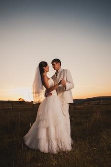 Couple de mariage dansant dans la colline de la montagne au coucher du soleil