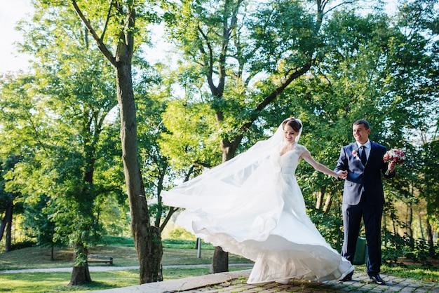 Couple de mariage dansant dans le parc