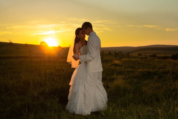 Le couple de mariage danse au coucher du soleil