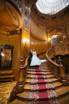 Couple de mariage élégant à l'ancienne maison vintage et palais avec de grands escaliers en bois