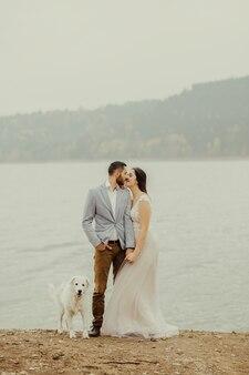 Couple de mariage embrassant près de la rive d'un lac de montagne avec leur chien