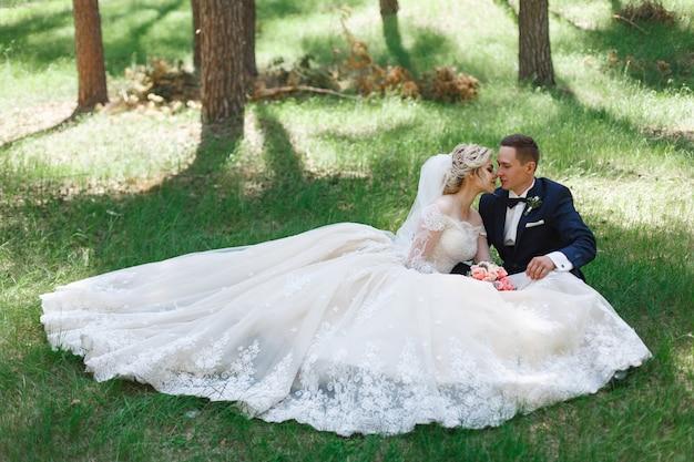 Couple de mariage émotionnel sur l'herbe verte au printemps. amour de deux personnes. mariée et le marié étreintes douces et baisers au jour du mariage dans la nature. portrait de beaux mariés en plein air. concept de mariage