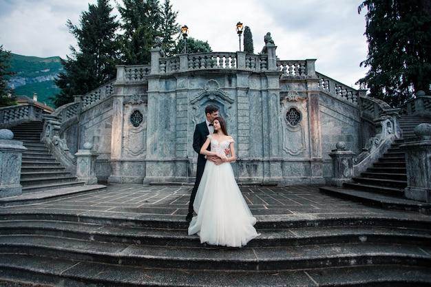 Couple de mariage sur les escaliers dans le parc