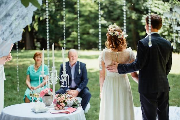 Couple de mariage est debout à côté de thei parents lors d'une cérémonie de mariage en plein air