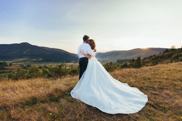 Couple de mariage étreignant sur fond de montagnes coucher de soleil