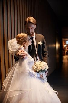 Couple de mariage étreindre et embrasser, le premier jour de la vie ensemble. jeunes mariés après la cérémonie de mariage, un beau couple s'aime et se fait des câlins