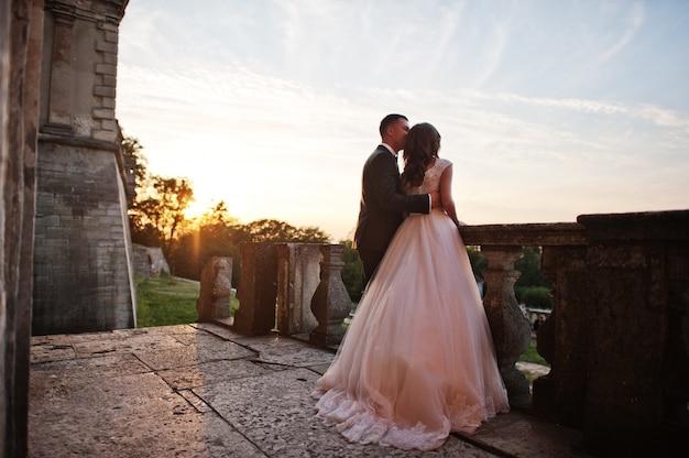 Couple de mariage fabuleux se promenant sur le territoire du château lors de leur journée de fête.