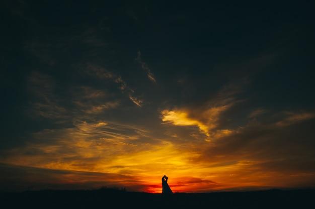 Couple de mariage sur fond de coucher de soleil