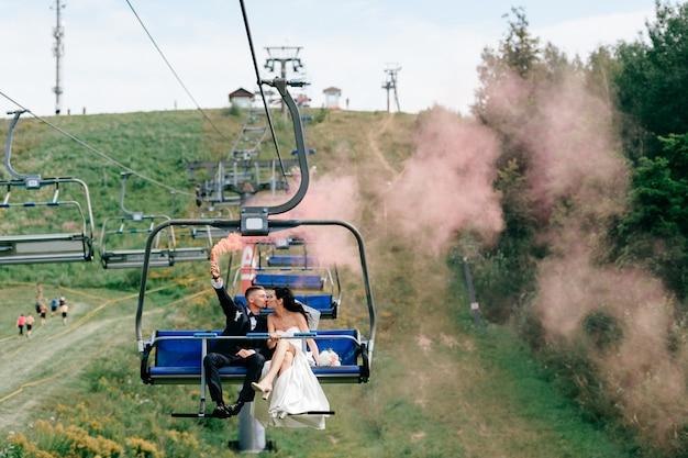 Couple de mariage heureux à cheval de téléphérique de montagne avec de la fumée colorée à la main.