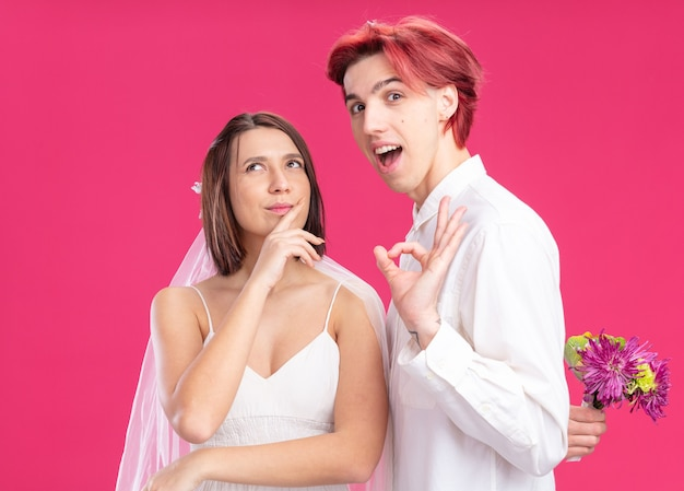 Couple de mariage heureux marié et mariée à la recherche de marié heureux et joyeux tenant des fleurs derrière pour sa mariée souriante en robe de mariée