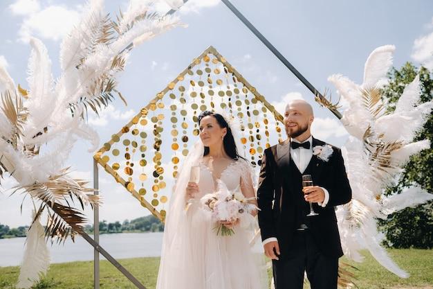 Couple de mariage heureux près de l'arche de mariage pendant la cérémonie.