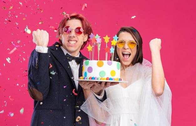 Couple de mariage heureux en robe de mariée portant des lunettes tenant un gâteau de mariage serrant les poings heureux et excité souriant gaiement debout sur rose