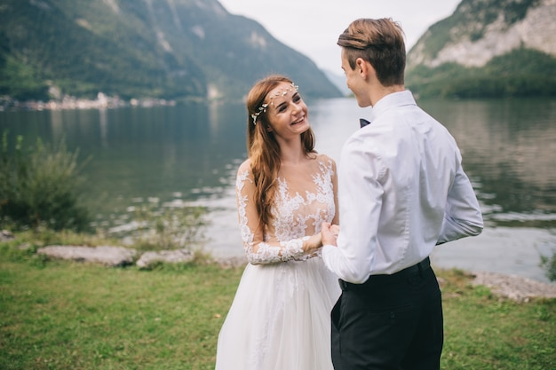 Un couple de mariage sur le lac et les montagnes de fond dans la ville de conte de fées d'autriche