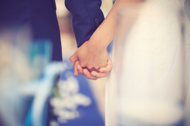 Couple de mariage main dans la main sur fond de coucher de soleil