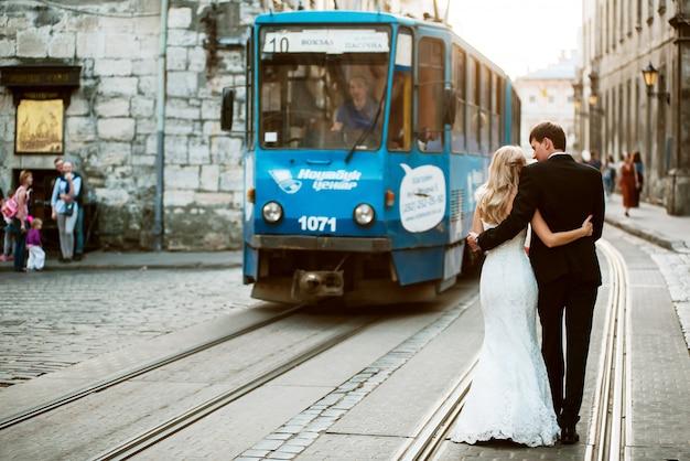 Couple de mariage marchant sur les voies de tram