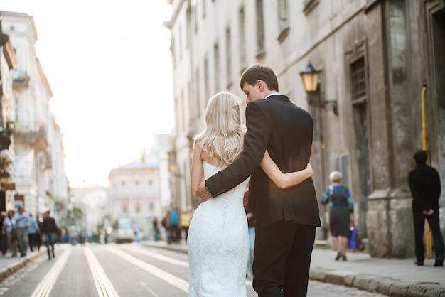 Couple de mariage marche sur les voies de tram