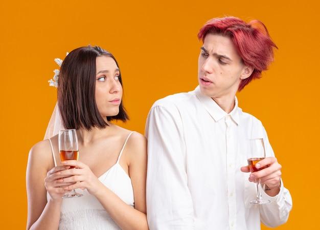 Couple de mariage marié et mariée en robe de mariée tenant des verres de champagne debout dos à dos offensé sur orange