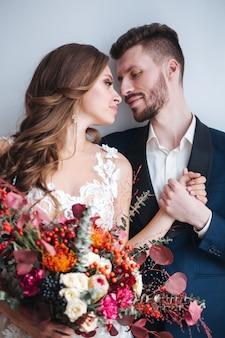 Couple de mariage avec mariée tenant le bouquet. portrait sensuel d'un jeune couple. photo de mariage en intérieur