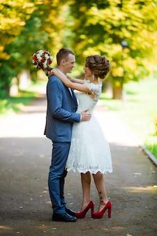 Couple de mariage, mariés heureux et mari étreignant dans le parc verdoyant.