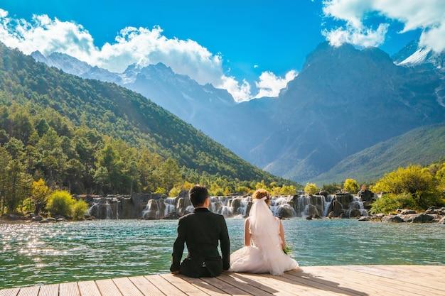 Couple de mariage, les mariés regardent la montagne cascade assis sur un pont en bois