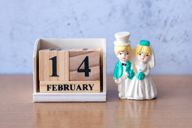 Couple de mariage miniature avec calendrier en bois 14 février. la saint-valentin