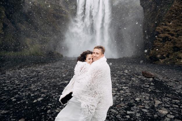 Couple de mariage près de la cascade de skogafoss les mariés recouverts d'une couverture en laine