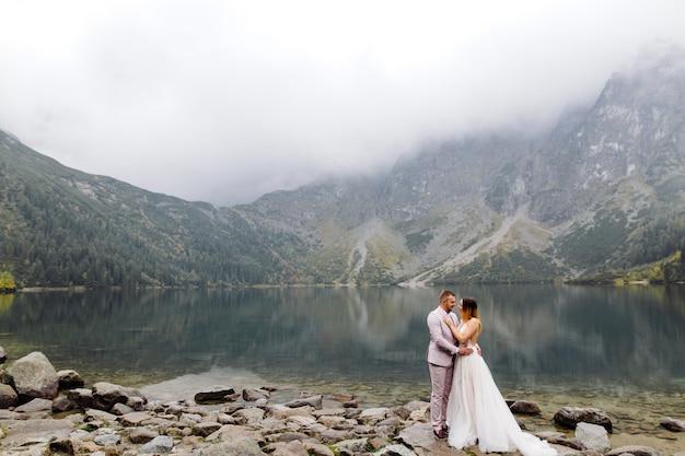 Couple de mariage romantique amoureux debout du lac sea eye en pologne. montagnes des tatras.