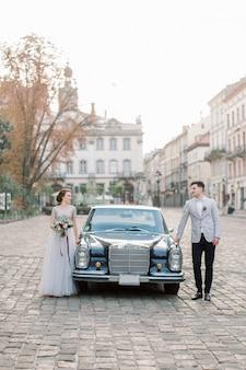 Couple de mariage romantique debout devant une voiture rétro noire, belle mariée et le marié heureux en été, les bâtiments de la vieille ville en arrière-plan