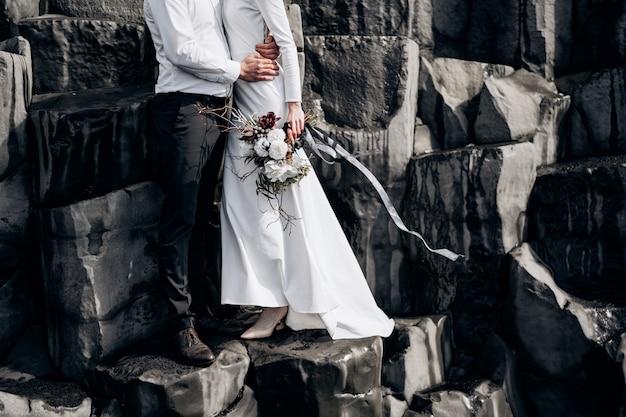 Un couple de mariage se dresse sur un mur de piliers en pierre que les mariés s'embrassent sur des kekurs de basalte