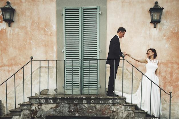 Couple de mariage se tient sur les traces devant une villa italienne orange