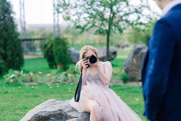 Couple de mariage sur une séance photo. la mariée tire le marié sur la caméra.