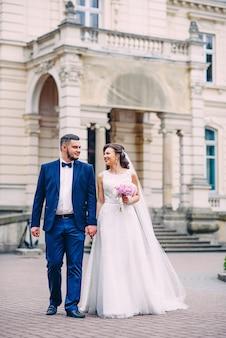 Couple de mariage sensuel marchant dans la cour du palais.