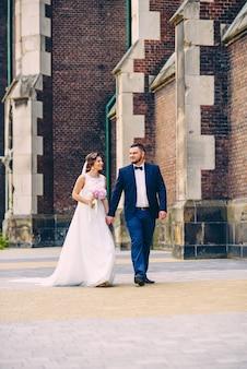 Couple de mariage sensuel marchant dans la rue près de l'ancien bâtiment historique