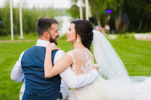 Couple de mariage souriant de l'arrière à l'extérieur