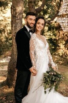 Couple de mariage souriant, mariage dans un style rustique, mariage dans la forêt.