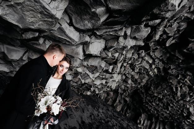 Couple de mariage sous un rocher de pierres de basalte mariés sur le