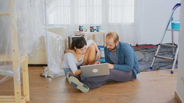 Couple marié achetant des outils de rénovation sur internet. redécoration d'appartements et construction de maisons tout en rénovant et en améliorant. réparation et décoration.