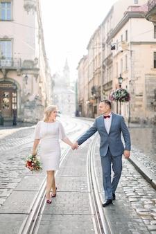 Couple marié d'âge moyen marchant main dans la main sur la voie du tramway sur la route pavée, dans la vieille ville antique