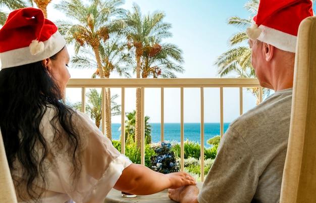 Un couple marié d'amoureux portant des chapeaux de père noël fête noël sur le balcon à une table donnant sur la mer. tir de dos. photo horizontale.