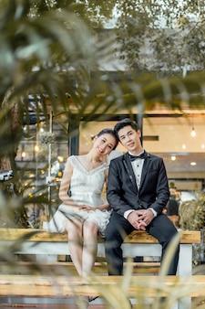 Un couple marié asiatique est assis ensemble dans un restaurant.