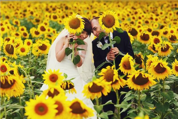 Couple marié drôle pose sur le champ tenant des tournesols