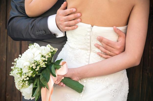 Couple marié embrassé, détail du buste et des bras