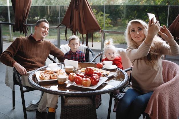 Un couple marié avec enfants, une fille et un fils prennent un selfie à une table dans un café. heureux couple traditionnel, bonheur familial.